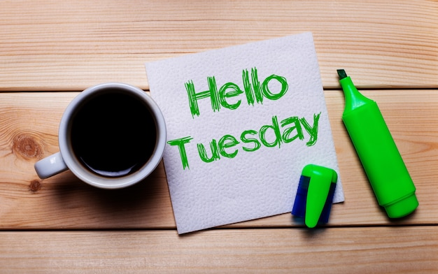 On a wooden table, a cup of coffee, a green marker and a napkin with the text hello tuesday