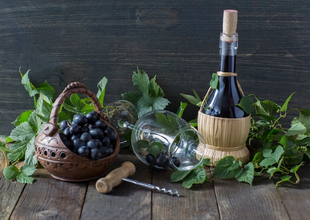 On a wooden table  dark grapes in a basket, red wine, a wine glass and a corkscrew