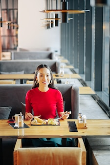 木製のテーブルレストランの木製のテーブルに座っている黒髪のスリムな魅力的な女性