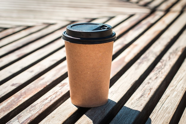 On a wooden table a disposable glass of coffee. craft eco friendly coffee mug. street food, cafe. coffee to go concept.