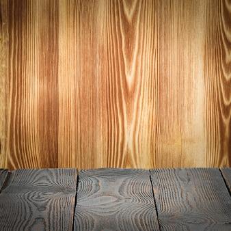 Деревянный настил стола на деревянном фоне. место для продукта, логотипа или этикетки. планировка, верстка.