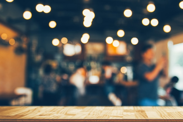 Wooden table in front of abstract blurred coffee shop lights backgroundâ