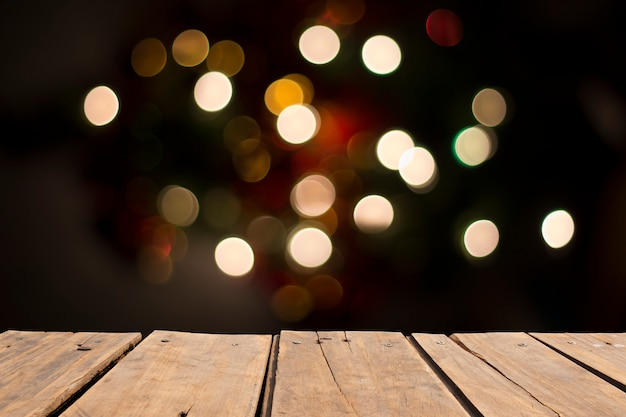 Wooden table in front of abstract blurred ligth