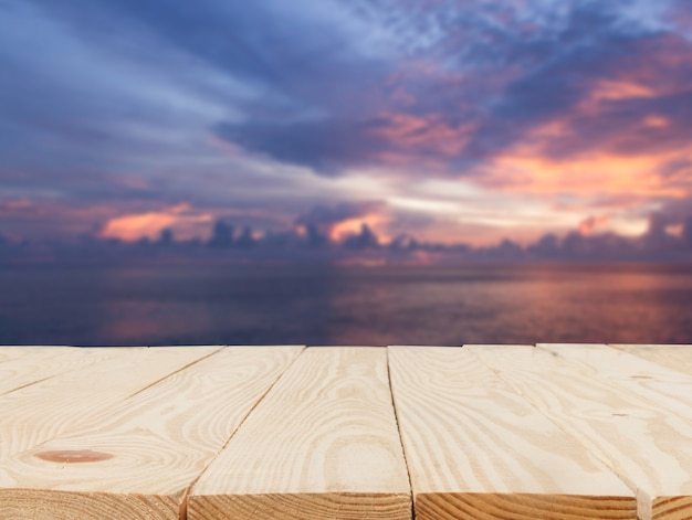 Wooden table in front of abstract blurred view of the light sunset over the sea background
