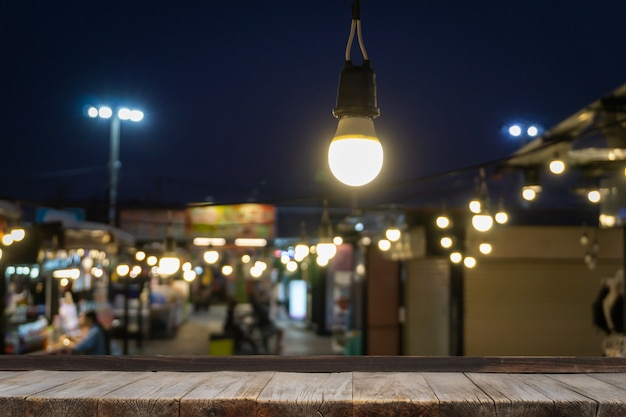 Wooden table in front of decorative outdoor string lights hanging on electricity post with blur people.