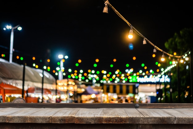 Wooden table in front of decorative outdoor string lights hanging on electricity post.