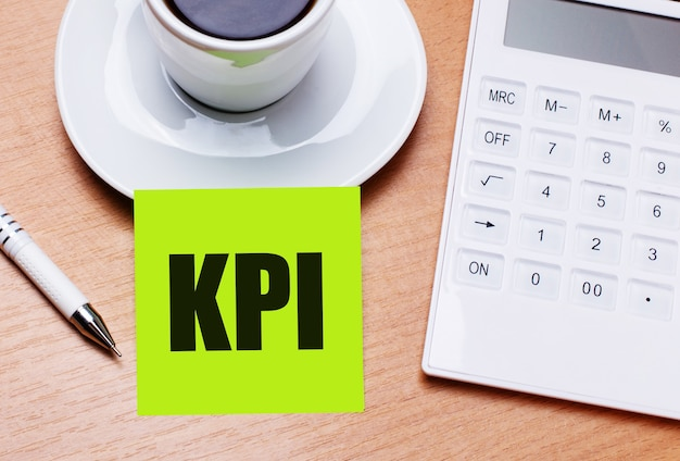 The wooden table has a white cup of coffee, a pen, a white calculator, and a green sticker with the text kpi. business concept