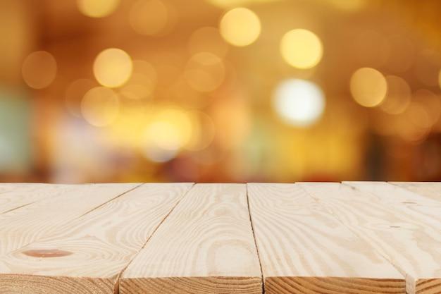 抽象的なぼやけたボケ背景の前に木製のテーブル