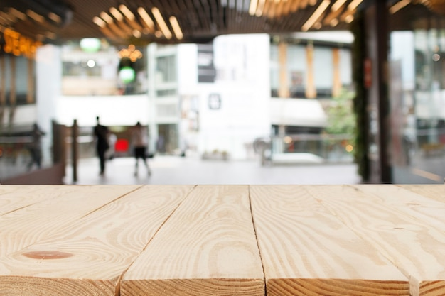 ショッピングモールの背景にぼやけた抽象的な前に木製のテーブル