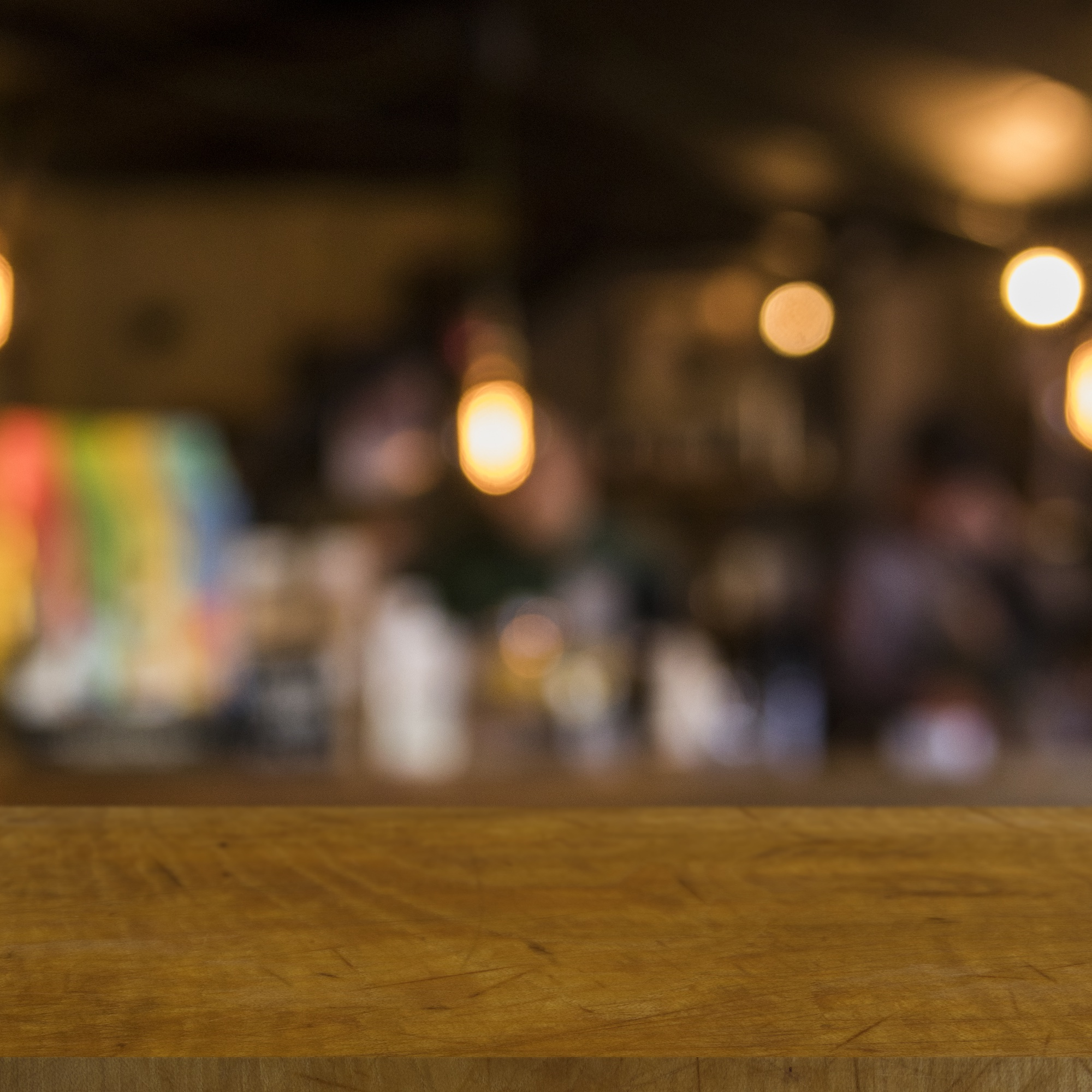 Wooden table in front of blurred restaurant lights