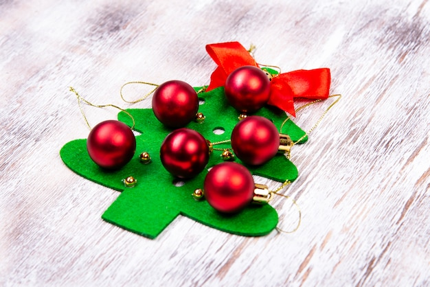 On a wooden table lies a felt christmas tree made by hands with red balls and a red bow at the top
