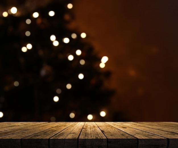 Tavolo in legno che si affaccia su un albero di natale defocussato