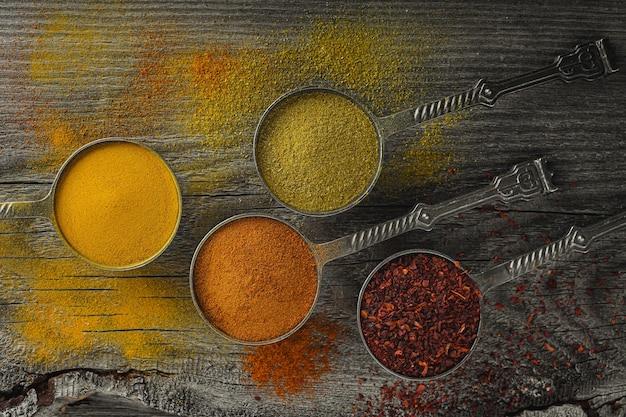 カラフルなスパイスの木製テーブル。食品、インド料理、カラフル、トップビューフレームスタイル