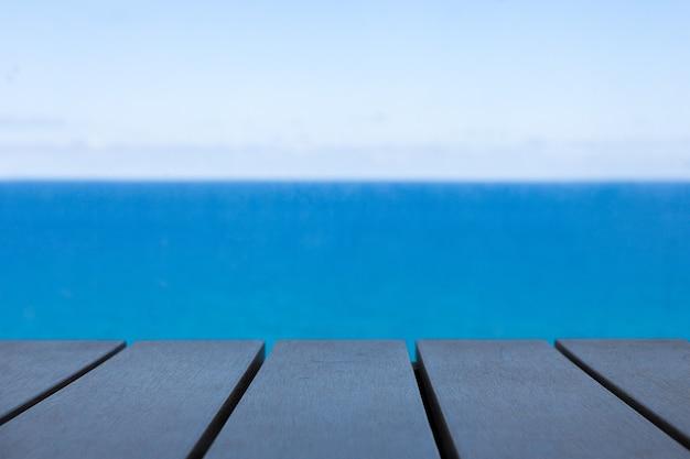 夏の青い海と空を背景に木製のテーブル