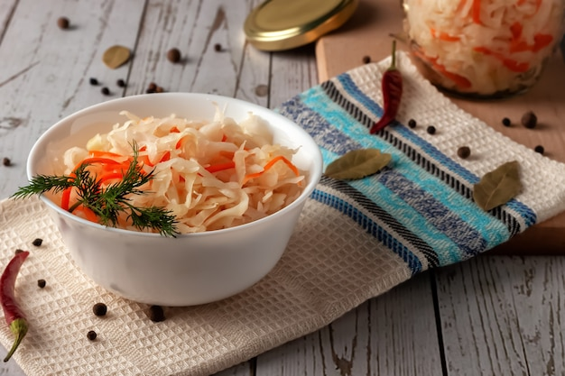 On a wooden table, sauerkraut with carrots and spices in a bowl. horizontal top view, rustic style