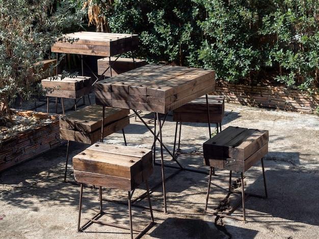 木製のテーブルセット。屋外の庭のコンクリートの床に黒い棒鋼の装飾で組み立てられた大胆な無垢材の板で作られた空のテーブルと椅子。