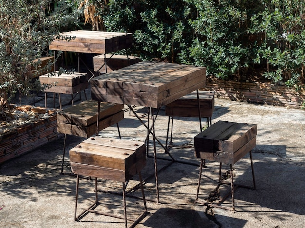 Wooden table set. empty table and chairs made by bold solid wood planks assembled with black steel bar decoration on concrete floor in the outdoor garden.