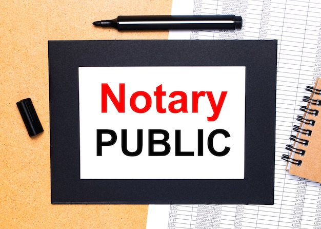 On a wooden table sheet of paper in a black frame with the text notary public