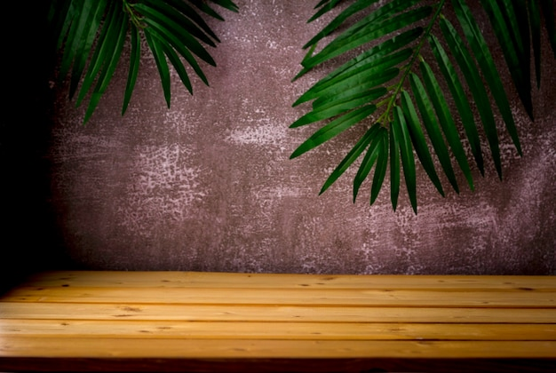 Wooden table for show product display and presentation, palm leaves and dark rugged background