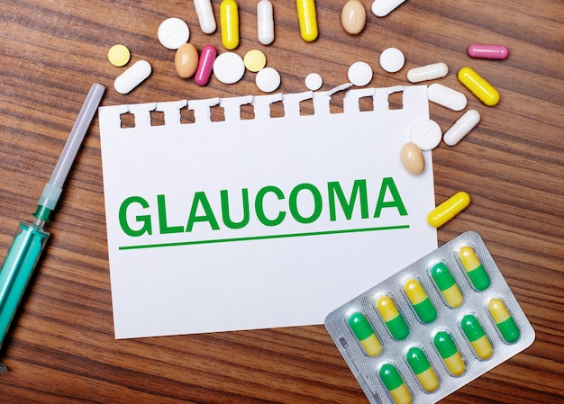 On a wooden table, a syringe, pills and a sheet of paper with the inscription glaucoma