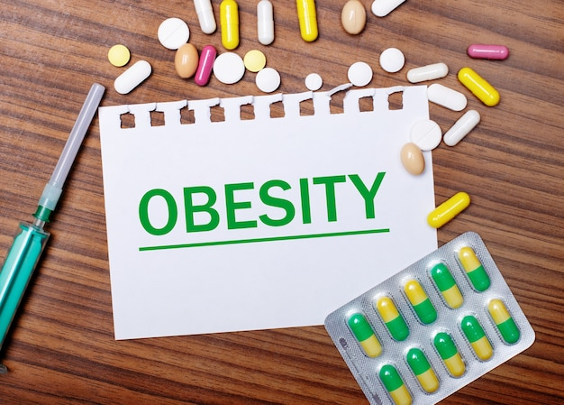 On a wooden table, a syringe, pills and a sheet of paper with the inscription obesity