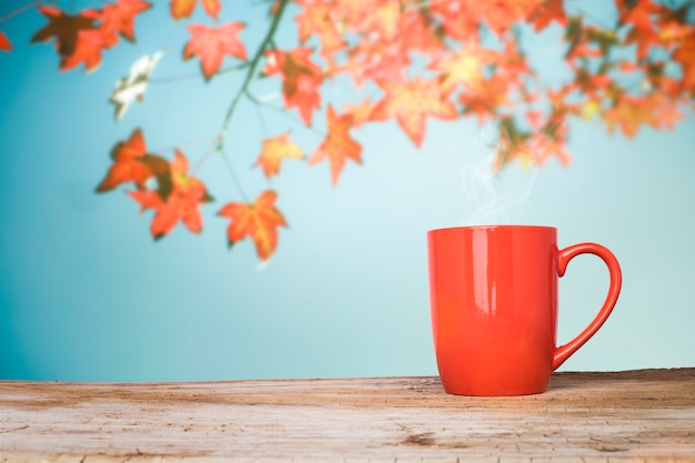 Wooden table or terrace and red leaves on blue sky background