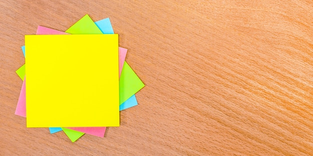 On a wooden table there are multicolored stickers with a place to insert text. template. copy space