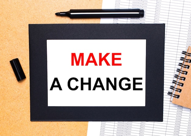 On a wooden table, there is a black open marker, a brown notepad and a sheet of paper in a black frame with the text make a change