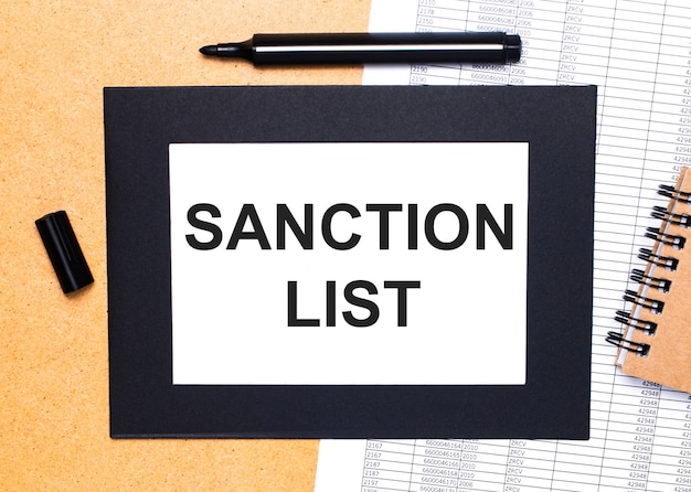 On a wooden table, there is a black open marker, a brown notepad and a sheet of paper in a black frame with the text sanction list