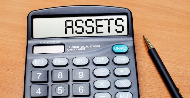 On a wooden table there is a black pen and a calculator with the text assets. business concept