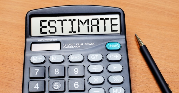 On a wooden table there is a black pen and a calculator with the text estimate. business concept