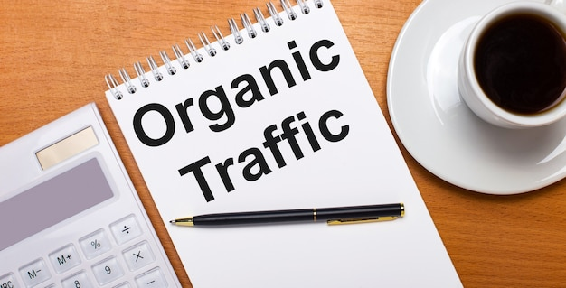 On a wooden table there is a white calculator, a white cup of coffee, a pen and a white notebook with the text organic traffic. business concept