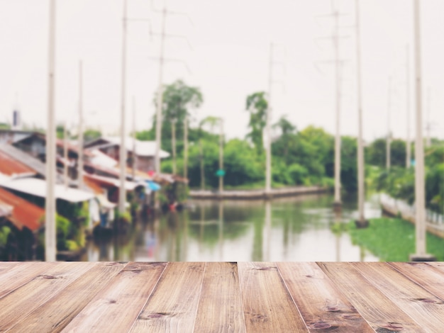 Wooden table top over abstract blur background of vintage riverfront house in thailand.