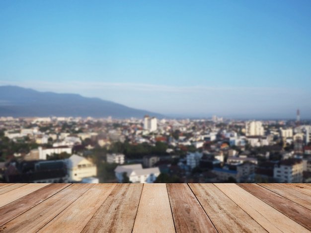 Wooden table top over blur background of cityscape and mountain in the morning.