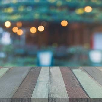 Wooden table top in front of garden with blurred bokeh lights