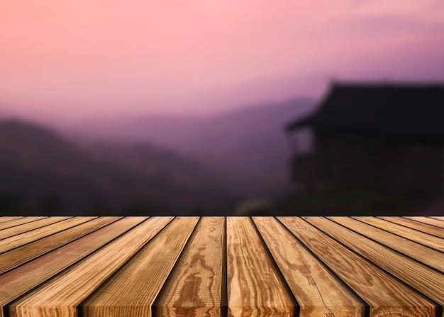 저녁에 화려한 하늘과 산이 있는 리조트의 흐릿한 장면에 있는 나무 탁자