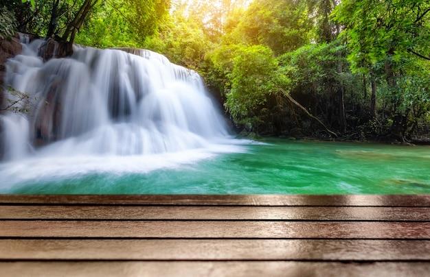 Деревянная столешница на фантастическом водопаде в тропическом лесу