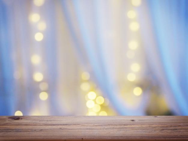 추상 위에 나무 테이블 상단 침실에 창에서 전구 bokeh와 흰색 커튼의 배경 흐림.