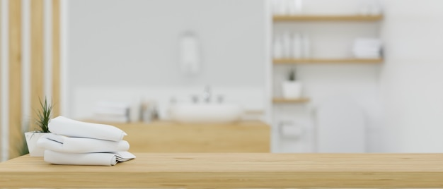 Wooden table top with bath towels over blurred white and wood minimalist bathroom interior 3d