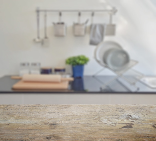 Wooden table top with blur of modern ceramic kitchenware and utensils on the countertop