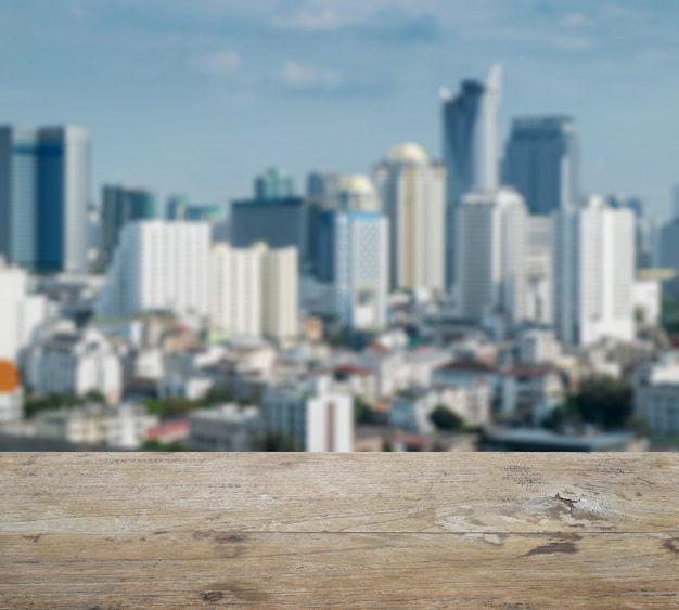 Wooden table top with blurred abstract background of bangkok downtown cityscape