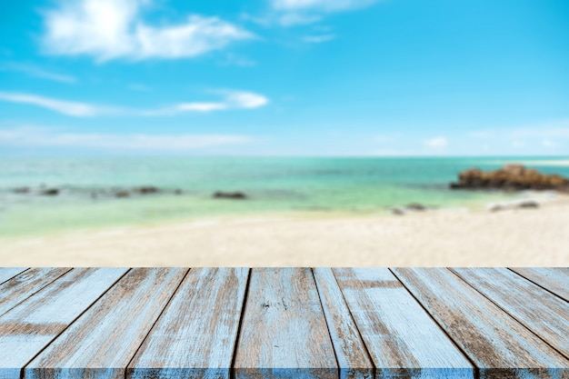 Wooden tabletop with blurred natural sea of tropical beach and blue sky, summer holiday background