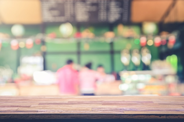 Wooden table top with view on defocused customer at restaurant