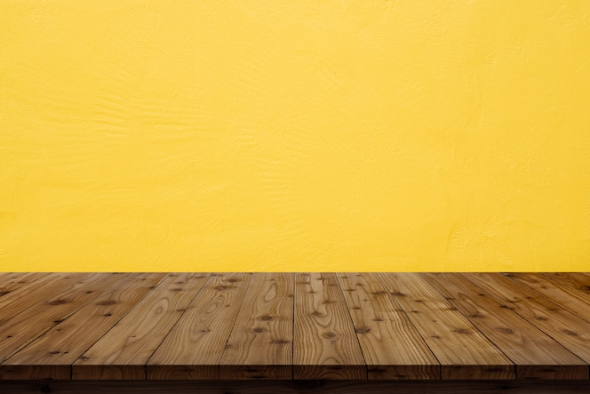 Wooden table top on yellow wall background.