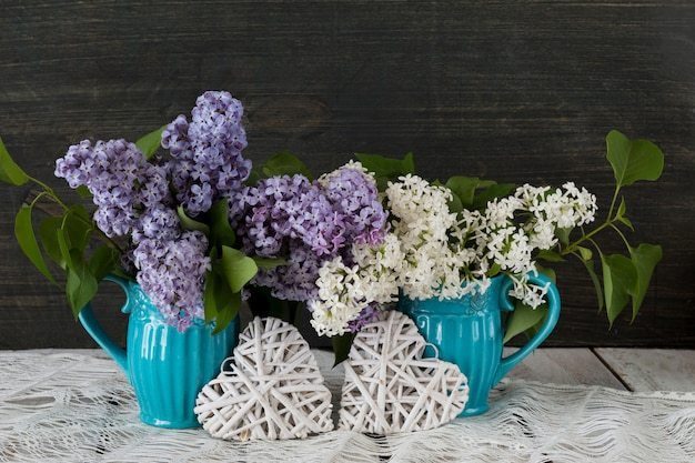 On a wooden table, two blue cups with a bouquet of lilac and two white wicker hearts