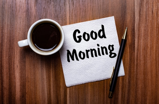 On a wooden table next to a white cup of coffee and a pen is a white paper napkin with the words good morning.