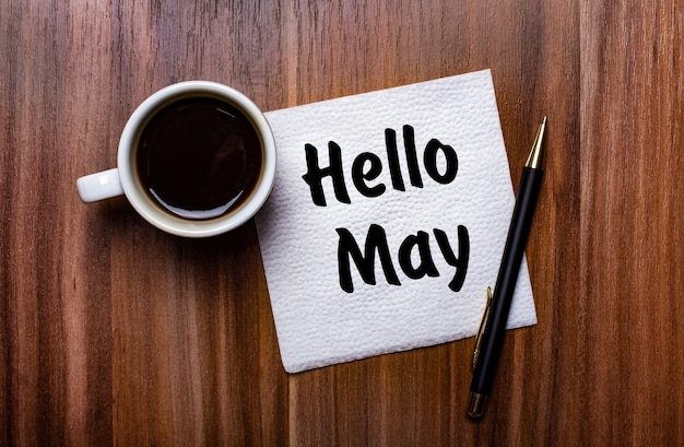 On a wooden table next to a white cup of coffee and a pen is a white paper napkin with the words hello may