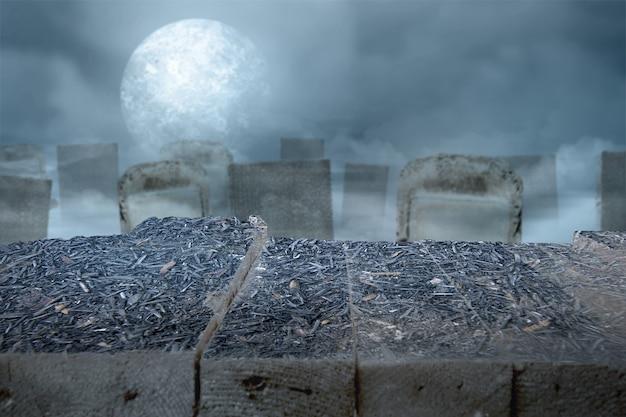 夜に墓地と満月の木製テーブル。ハロウィーンのコンセプト