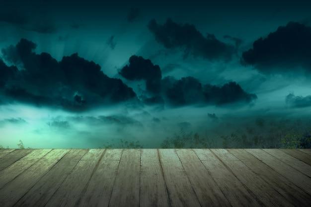 Деревянный стол с полной луной с темными облаками ночью. концепция хэллоуина