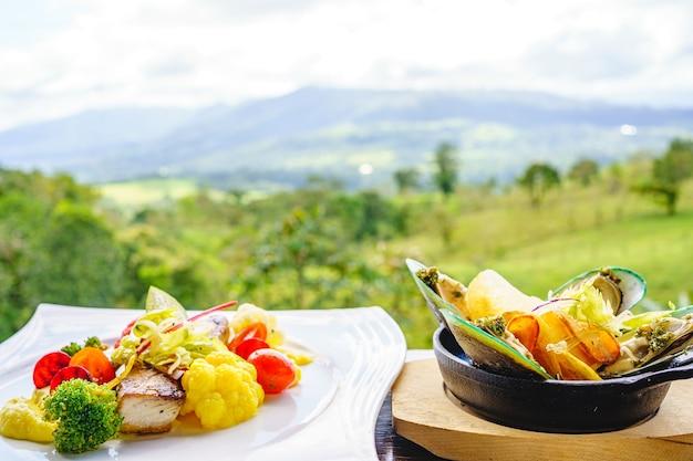 Деревянный стол с тарелкой рыбного филе и тарелкой маринованных мидий на фоне леса